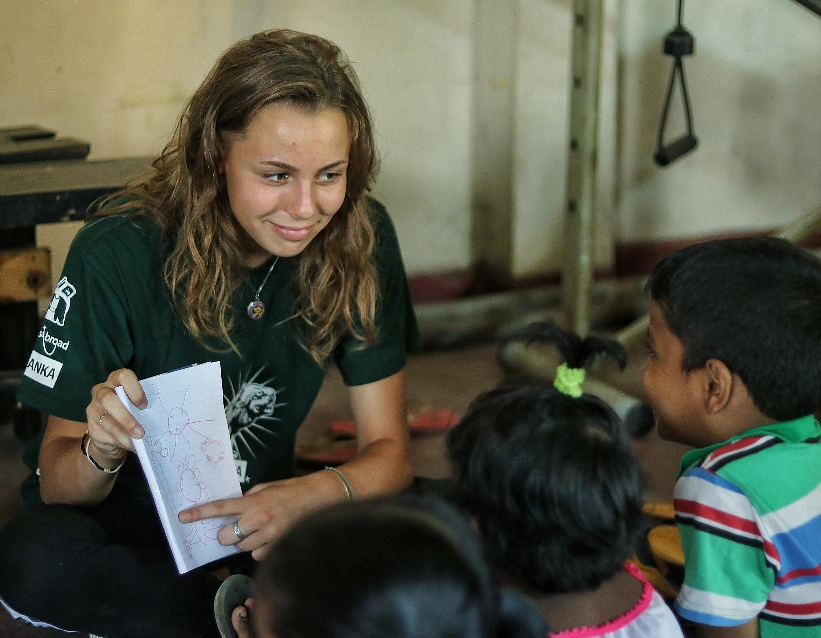 Projects Abroad volunteer with children in Sri Lanka teaches English to young children at her Childcare placement.